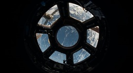 Inside a spaceship looking through a window back towards to Earth.