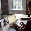 Photo of man sat at a desk on an apple mac laptop