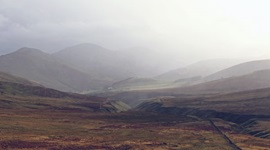 Landscape shot of peatland in a valley, with mountains in the misty background.