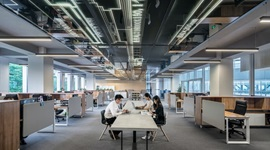 Office space- people working at rows of desks.