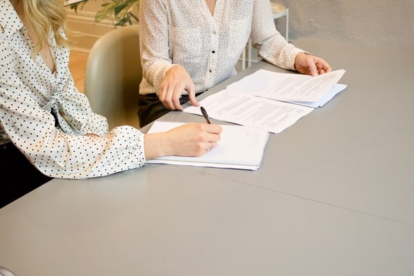 2 women talking at a desk over pages of notes.