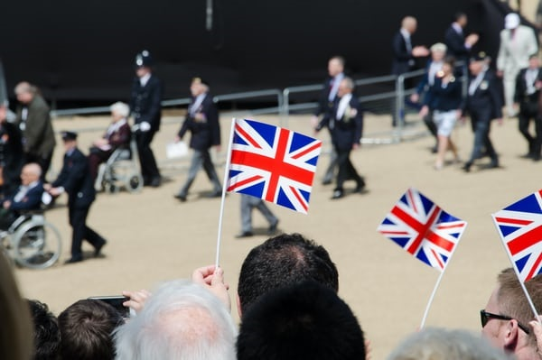 British flags being waved in front of blurred lines of veterans.