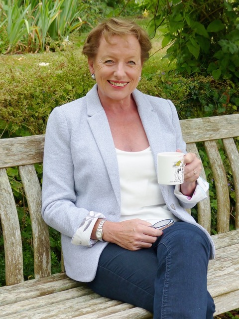 Hilary Shenton from Women in Rural Enterprise is sitting on a bench with a cup of tea smiling